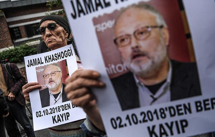 In an October 9 file photo, protesters outside the Saudi consulate in Istanbul hold portraits of critical Saudi journalist Jamal Khashoggi. Saudi Arabia today said the journalist was killed during a fight in the consulate. (AFP/Ozan Kose)
