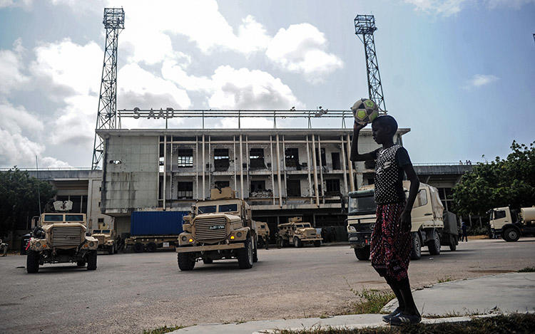 A Somali boy, pictured in August 2018, watches as soldiers for the African Union Mission leave the Mogadishu stadium they used for years as a base. Gunmen in October shot dead a radio journalist in a town about 17km from the capital. (AFP/Mohamed Abdiwahab)