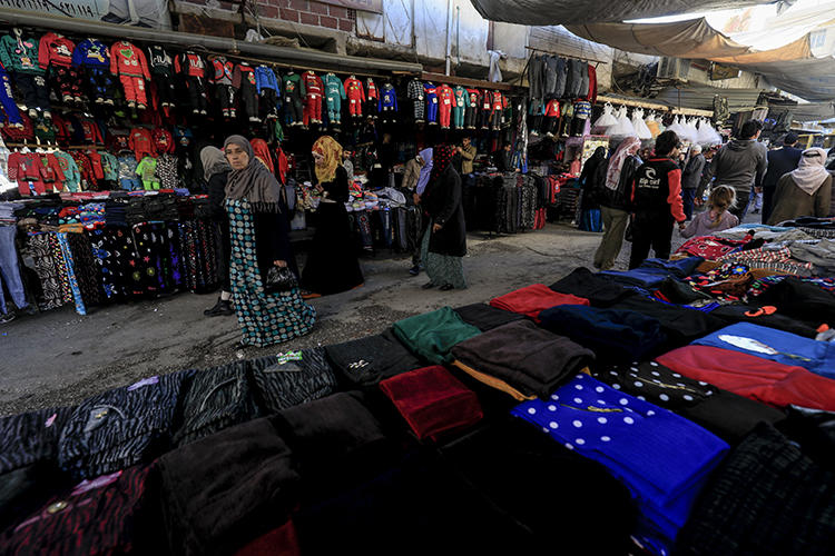 Shoppers walk on a market street in the northeastern Syrian town of Qamishli on May 2, 2018. A prominent Syrian writer was arrested and held for five days in the town in late September and early October 2018. (AFP/Delil Souleiman)