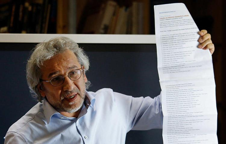 Exiled journalist Can Dündar holds up a list of journalists jailed in Turkey, during a September 28 press conference in Berlin. Prosecutors have asked for Interpol to issue a warrant for Dündar's arrest. (AFP/David Gannon)