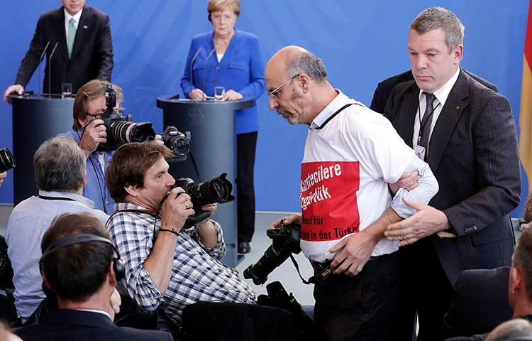 A Turkish man in a 'freedom for journalists' T-shirt is thrown out of a press conference for Turkey's President Recep Tayyip Erdoğan and German Chancellor Angela Merkel in Berlin on September 28. (AP/Michael Sohn)