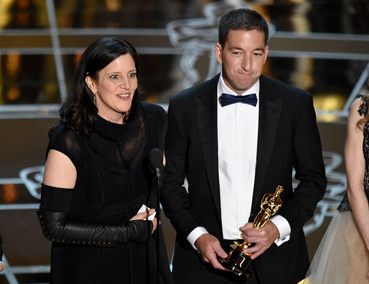Filmmaker Laura Poitras and journalist Glenn Greenwald receive the Oscar for best documentary, for their film Citzenfour in February 2015. Poitras says repeated border stops led to her editing the film outside of the U.S. (AP/ John Shearer/Invision)