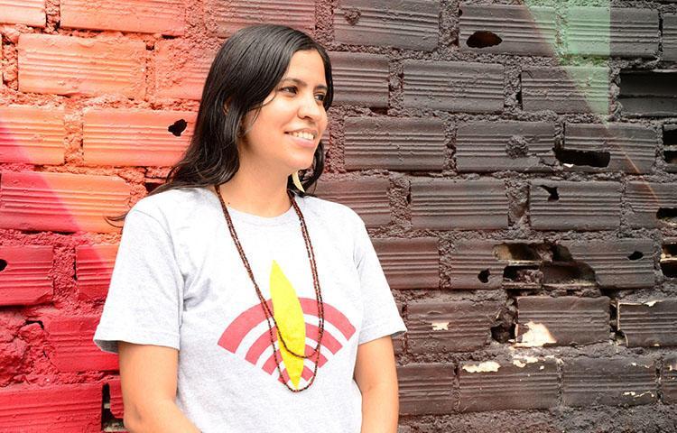 Renata Machado, fundadora da Rádio Yandê, na foto com o logotipo da estação. A Rádio Yandê é um dos poucos veículos que conta as histórias dos povos indígenas do Brasil em seus próprios termos. (Alfredo Boc Boc)
