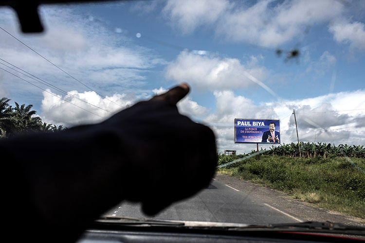 A taxi driver points towards an electoral poster for Cameroonian President Paul Biya as the road crosses into the majority English-speaking South West region of Cameroon, in Buea, on October 3, 2018. A journalist was detained October 23 after publishing articles criticizing the government's handling of grievances of Anglophone Cameroonians. (AFP/Marco Longari)