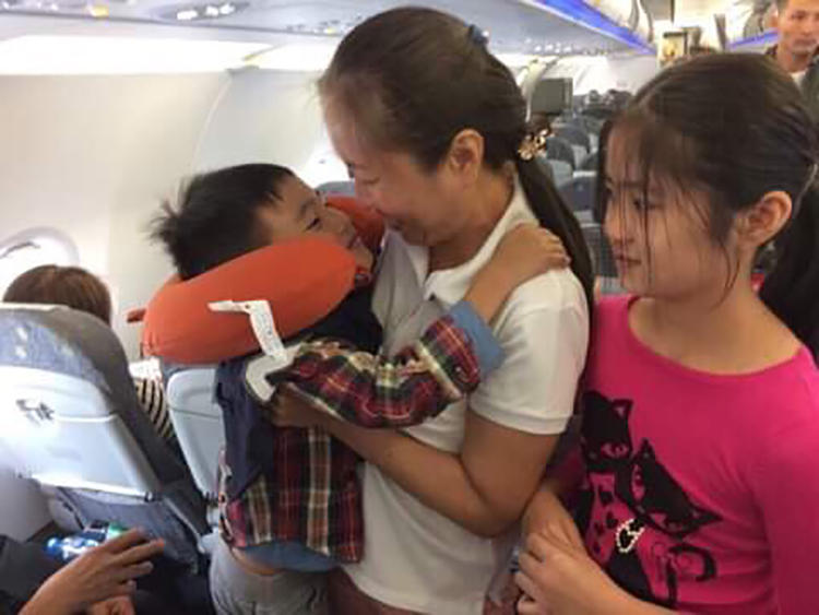 "Vietnamese blogger Nguyen Ngoc Nhu Quynh, known by her pen name ""Mother Mushroom,"" with her two children on a plane on the way to the U.S. after being freed from prison in Vietnam on October 17, 2018. (Family photo)"
