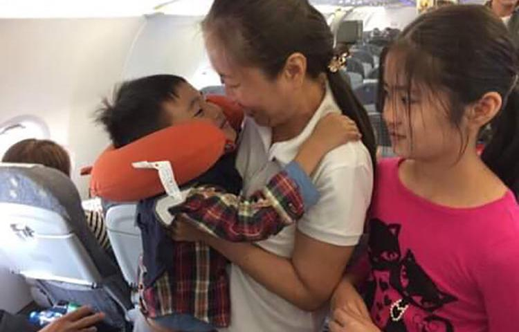 """Vietnamese blogger Nguyen Ngoc Nhu Quynh, known by her pen name """"Mother Mushroom,"""" with her two children on a plane on the way to the U.S. after being freed from prison in Vietnam on October 17, 2018. (Family photo)"""