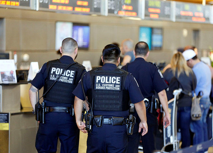 Customs and Border Protection agents pictured at Los Angeles International Airport in January 2017. The agency's power to search electronic devices without warrant has serious implications for press freedom. (Reuters/Patrick T. Fallon)