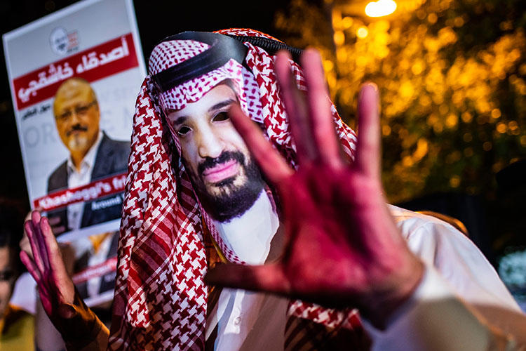 A protester wears a mask depicting Saudi Crown Prince Mohammed Bin Salman with painted hands next to people holding posters of Saudi journalist Jamal Khashoggi during the demonstration outside the Saudi Arabian consulate in Istanbul on October 25, 2018. (AFP/Yasin Akgul)