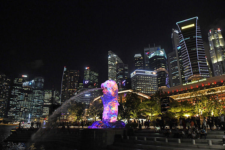 Singapore's Merlion statue is lit up in front of the city skyline in March 2018. Authorities are investigating a criminal defamation complaint against an independent news website. (AFP/Roslan Rahman)
