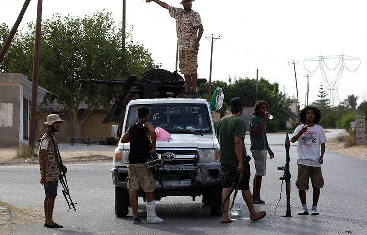 Militiamen loyal to the Government of National Accord (GNA), Libya's internationally recognized government, keep watch in Tripoli on September 25, 2018. Authorities in Ajilat, a city under GNA rule, are taking legal action against a journalist who reports on corruption. (AFP/Mahmud Turkia)