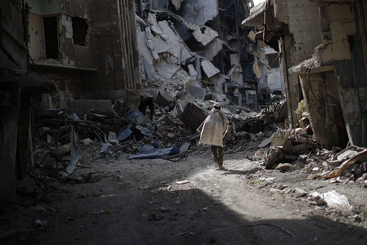 A man walks through rubble in Damascus in October 2018, caused by years of war. Safety remains a key concern for Syrian journalists. (AP/Hassan Ammar)