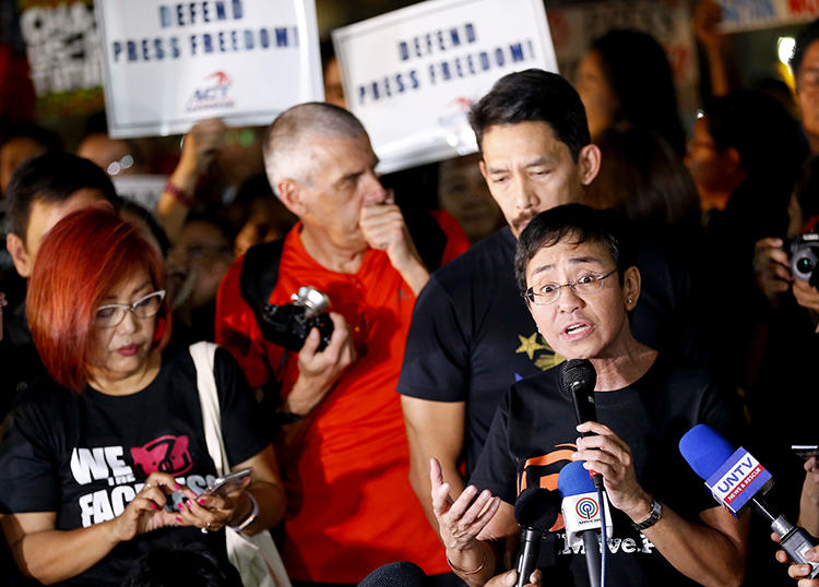 Maria Ressa, right, CEO of Rappler, an online news agency, addresses a rally of journalists and supporters during a protest against the Securities and Exchange Commission's order to revoke its registration on January 19, 2018, northeast of Manila, Philippines. Philippine authorities in November 2018 threatened to charge Ressa and Rappler with tax evasion. (AP Photo/Bullit Marquez)