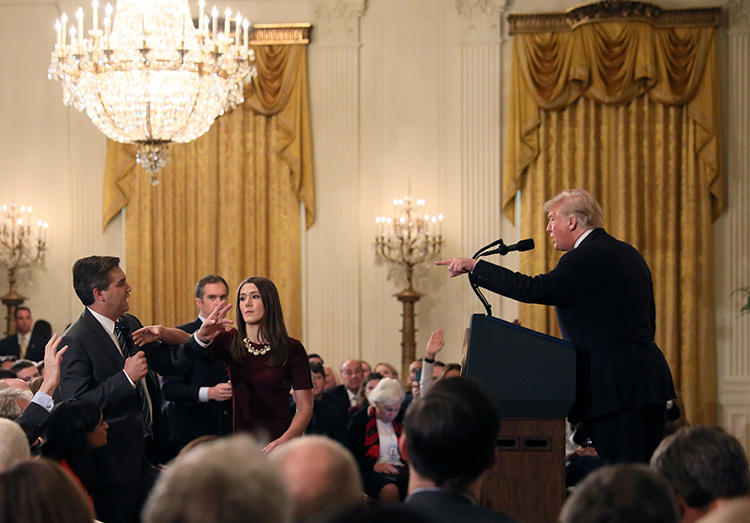 A White House staff member reaches for the microphone held by CNN's Jim Acosta as he questions President Donald Trump during a news conference at the White House in Washington, D.C., on November 7, 2018. The White House revoked Acosta's credentials later that day. (Reuters/Jonathan Ernst)