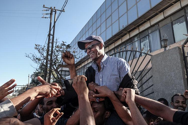 الصحفي إسكندر نيغا محمولاً على أكتاف مؤيديه في فبراير/ شباط 2018، وقد أفرجت عنه السلطات بعد أن حكم عليه بالسجن لمدة 18 سنة. وللمرة الأولى منذ عام 2004، لم يتضمن إحصاء لجنة حماية الصحفيين السنوي أي صحفي سجين بسبب عمله في إثيوبيا. (وكالة الأنباء الفرنسية/ يوناس تاديسي)