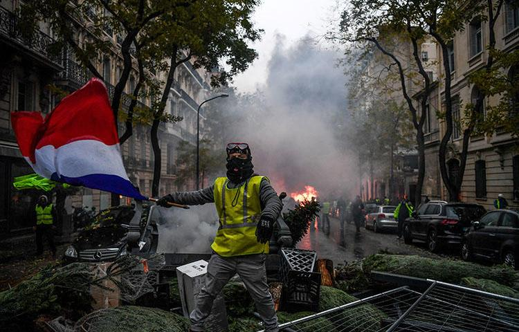 A protester waves the French flag during a rally in Paris on December 1 against a proposed fuel tax hike. Journalists covering the unrest across France and Belgium are at risk of being attacked and injured. (AFP/Alain Jocard)