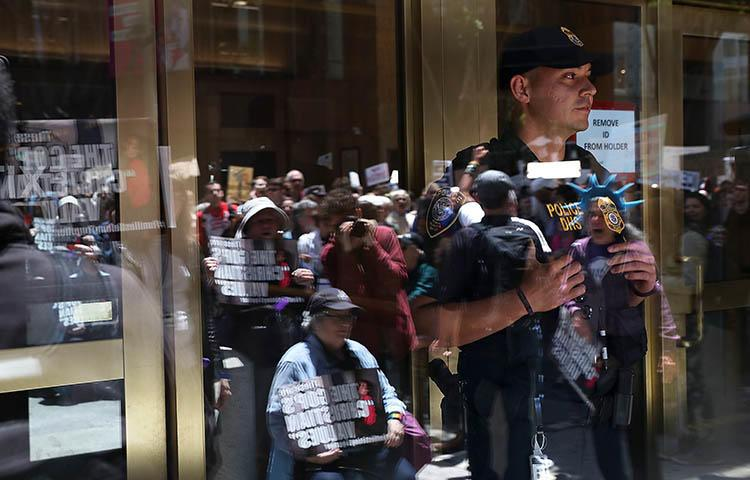 An ICE agent monitors a protest outside the department's office in San Francisco in June over President Trump's immigration policy. Journalists who fled threats in their home countries are being held in prolonged ICE detention while authorities review their asylum requests. (Getty Images North America/AFP/Justin Sullivan)