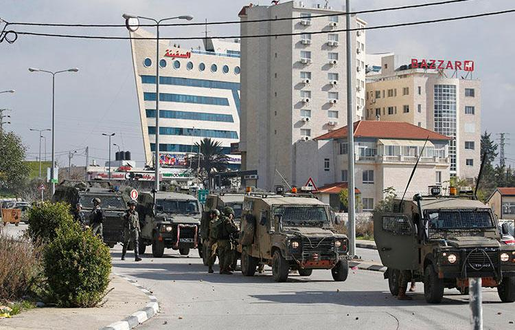 Israeli soldiers deploy during clashes in the West Bank city of Ramallah following a raid on December 10, 2018, one day after a drive-by shooting attack next to a settlement in which many Israelis were injured. Israeli forces raided the offices of the official Palestinian news agency, and detained a Palestinian journalist. (AFP/Abbas Momani)