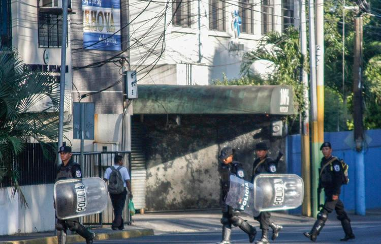 Riot police walk in front of the 100% Noticias cable and internet news station in Managua on December 22, 2018, a day after the station was raided and closed by the Nicaraguan police. Two journalists were arrested during the raid. (AFP/Maynor Valenzuela)