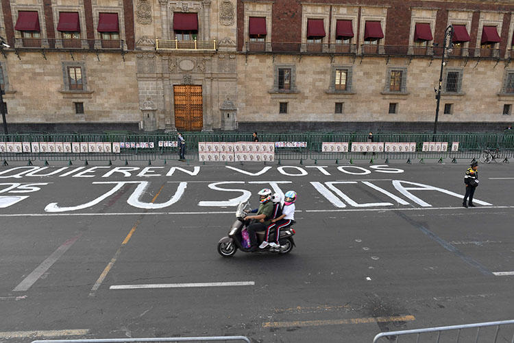 A police officer stands guard after members of the press wrote messages on the street during a protest against the murder or disappearance of more than 140 journalists in Mexico since 2000, in front of the National Palace in Mexico City on June 1, 2018. The body of journalist Alejandro Márquez Jiménez was found on December 1, 2018, near Tepic, the capital of the northwestern state of Nayarit. (AFP/Yuri Cortez)