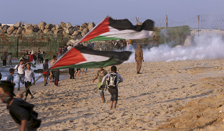 Protesters take cover from teargas fired by Israeli troops near the fence of the Gaza Strip border with Israel during a protest on the beach near Beit Lahiya, northern Gaza Strip, on November 19, 2018. (AP Photo/Adel Hana)