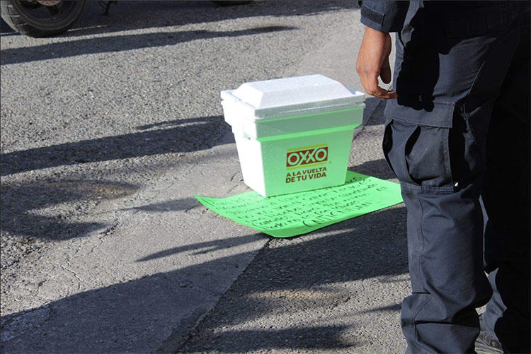 An icebox containing a head, and a threatening note are left outside the office of Mexican paper Expreso on December 20. (Periodistas Desplazados México)