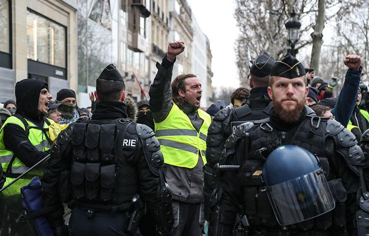 A protester raises his fist in front of security forces during a demonstration in Paris on December 15, 2018, to protest rising costs of living and high taxes. Dozens of journalists have been attacked and some injured by both protesters and police. (Zakaria Abdelkafi/AFP)