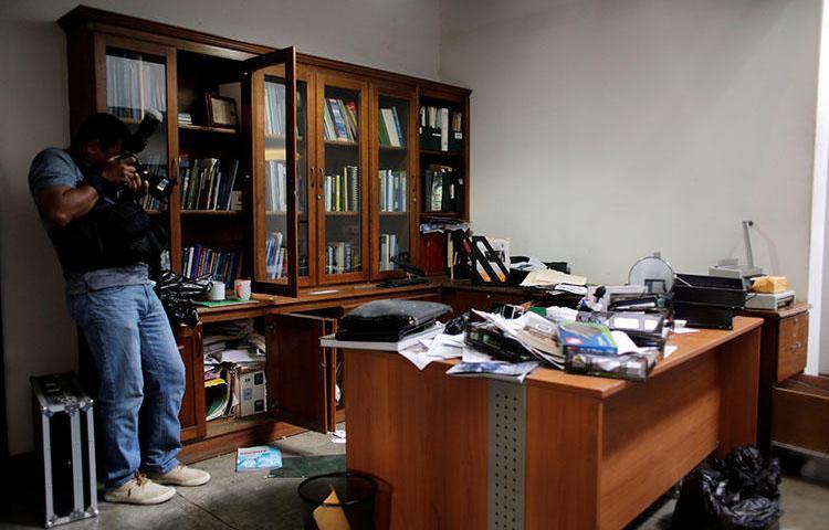 Fotógrafo local faz um vídeo do escritório do jornalista Carlos Fernando Chamorro no dia seguinte à invasão pela polícia nacional em Manágua, na Nicarágua. (REUTERS/Oswaldo Rivas)