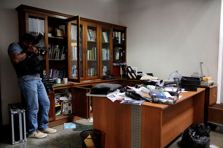 A local photographer makes a video of journalist Carlos Fernando Chamorro's office the day after it was raided by the national police in Managua, Nicaragua. (REUTERS/Oswaldo Rivas)