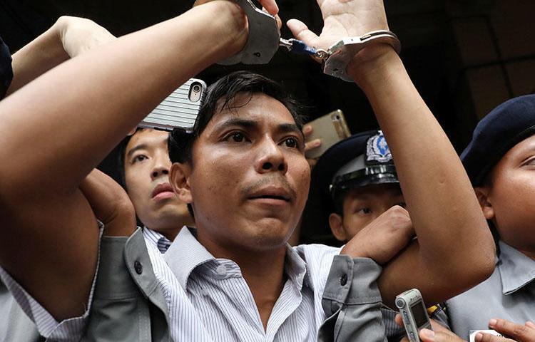 Reuters muhabiri Kyaw Soe Oo Yagnon'daki mahkemeye kelepçeli şekilde götürülüyor. O ve meslektaşı Wa Lone Myanmar'da yedişer yıl hapse mahkum oldular.  (Reuters/Ann Wang)