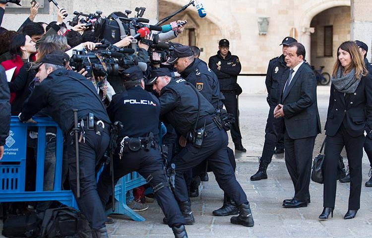 Agentes policiales se ubican entre periodistas y la procuradora pública española en las afueras de los tribunales de Palma de Mallorca, en la isla de Mallorca en febrero 2017. En diciembre 2018, agentes policiales confiscaron equipos y documentos de dos agencias de noticias en conexión con una investigación sobre información filtrada. (Jaime Reina/AFP)