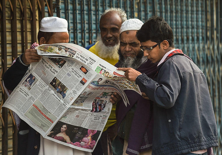 People read a newspaper carrying headlines of the general election results in Dhaka on December 31, 2018. Several journalists were attacked and one was detained while covering the vote. (AFP/Indranil Mukherjee)