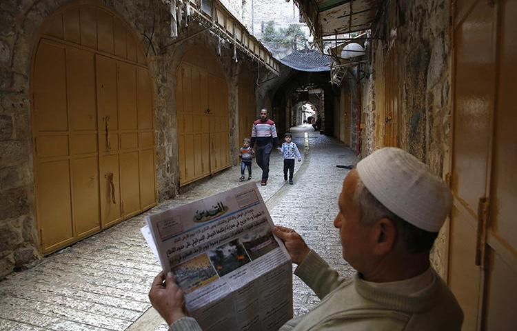 A Palestinian man reads a newspaper on March 31, 2018. A reporter for the London-based Quds Press News Agency, Yousef al-Faqeeh, was recently detained in the West Bank. (Hazem Bader/AFP)