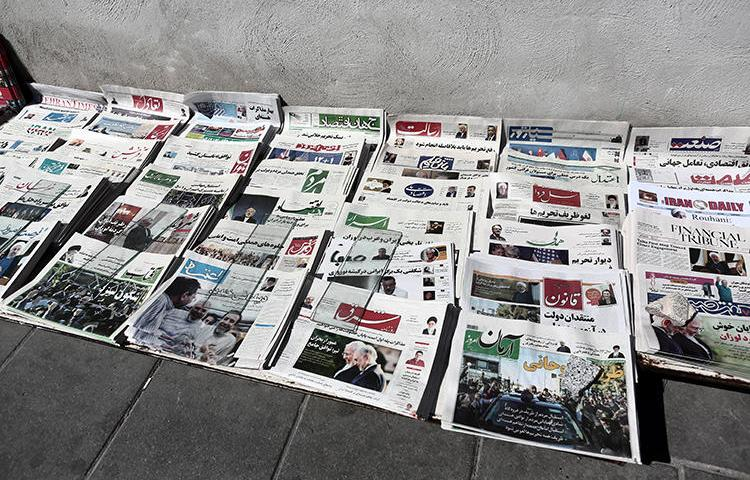Iranian newspapers lay on the ground in front of a kiosk in Tehran on April 4, 2015. On January 23, 2019, journalist Yashar Soltani, who reported on corruption in Tehran land deals, was sentenced to five years in prison. (Behrouz Mehri/AFP)