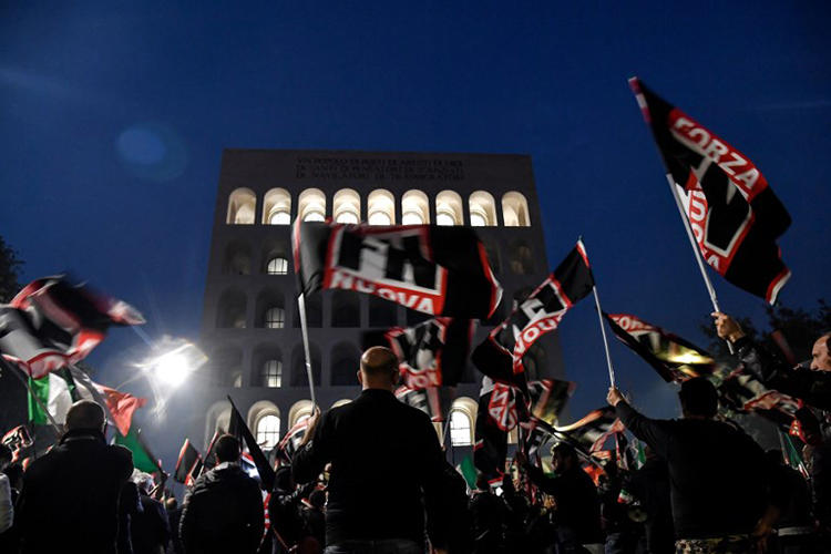 Members of the Italian far-right political party Forza Nuova wave flags during a demonstration on November 4, 2017, in central Rome. On January 7, 2019, members of Forza Nouva and other extremist groups attacked two reporters covering an event in Rome. (AFP/Andreas Solaro)