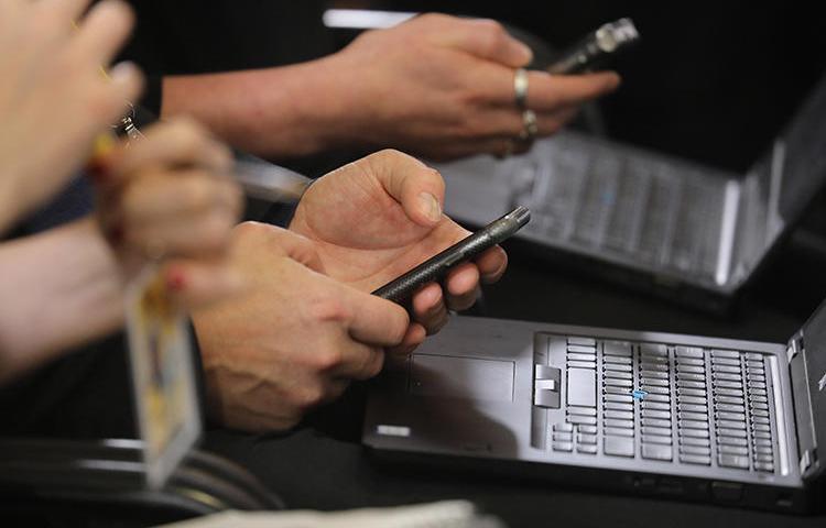 Jornalistas trabalham em seus telefones e laptops durante uma coletiva de imprensa em Bruxelas, em dezembro. Os hackers estão usando métodos sofisticados de phishing para tentar acessar as contas de repórteres e defensores dos direitos humanos (AFP/Ludovic Marin)