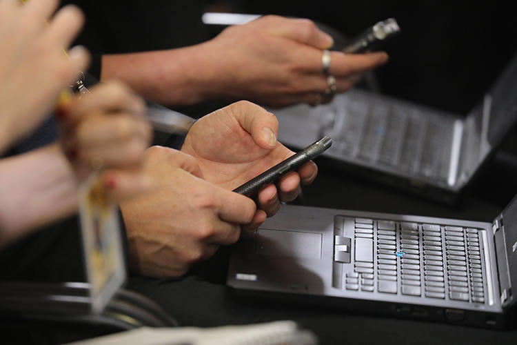 Journalists work on their phones and laptops during a press conference in Brussels in December. Hackers are using sophisticated phishing methods to try to access the accounts of reporters and human rights defenders. (AFP/Ludovic Marin)