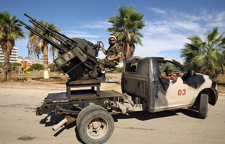 Members of Libyan security forces loyal to Libyan National Army head Khalifa Haftar operate turrets mounted on pickup trucks in eastern Libya in October 2018. A photojournalist was detained on December 20, 2018, in the eastern city of Ajdabiya. (AFP/Abdullah Doma)