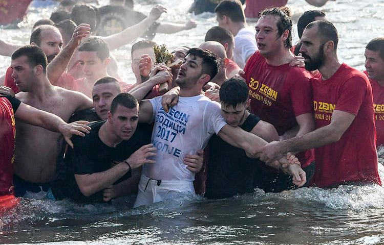 Participants in a religious event pull a cross out of the river Vardar in Skopje during Epiphany on January 19. A journalist covering the event says a security guard attacked her when she tried to interview one of the people taking part. (AFP/Robert Atanasovski)