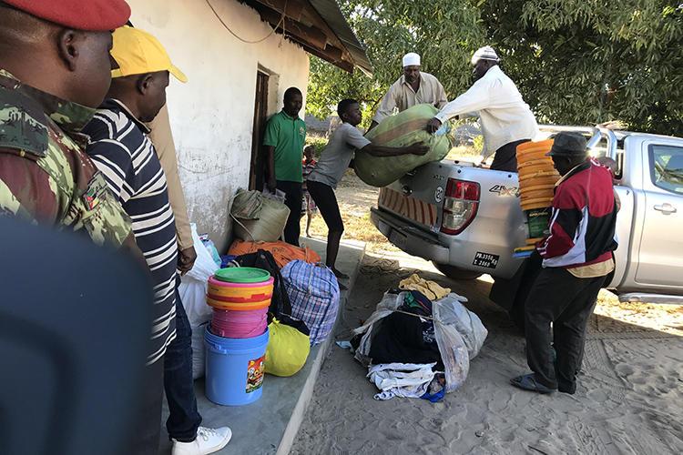 Deslocados internos descarregam comida, cobertores e outros bens depois de fugirem dos ataques de combatentes em Naunde, no norte de Moçambique, em 13 de junho de 2018. Um jornalista moçambicano foi detido em 5 de janeiro de 2019 e mantido numa prisão militar depois de fotografar famílias que fugiram de ataques de militantes. (AFP/Joaquim Nhamirre)