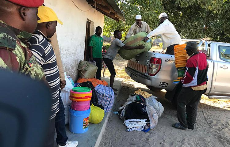 Internally displaced people offload food, blankets, and other goods after fleeing militant attacks in Naunde, northern Mozambique, on June 13, 2018. A Mozambican journalist was arrested on January 5, 2019, and held in a military prison after photographing families who fled the militant attacks. (AFP/Joaquim Nhamirre)