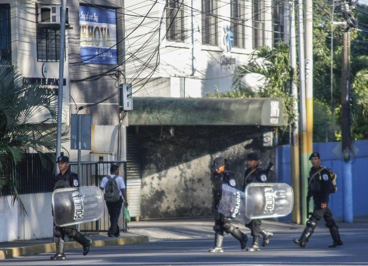 Policiais do choque caminham em frente à estação noticiosa a cabo e internet 100% Noticias, em Manágua, em 22 de dezembro de 2018, um dia depois de a emissora ter sido invadida e fechada pela polícia nicaraguense. Dois jornalistas foram presos durante a incursão. (AFP / Maynor Valenzuela)