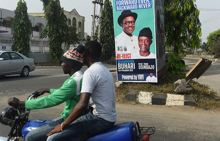 A campaign poster for Nigeria's incumbent president and candidate Muhammadu Buhari and his Vice-President Yemi Osinbajo, pictured in Lagos, on January 4. At least three journalists were injured by stray bullets after a fight broke out at a campaign rally for the ruling APC party. (AFP/Pius Utomi Ekpei)