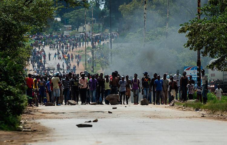 Protesters block the main route to Zimbabwe's capital Harare from Epworth township on January 14, 2019, after the government more than doubled the price of fuel. On January 15, CPJ joined more than 20 rights organizations and the #KeepItOn Coalition to call for authorities in Zimbabwe to restore internet and social media services. (AFP/Jekesai Njikizana)