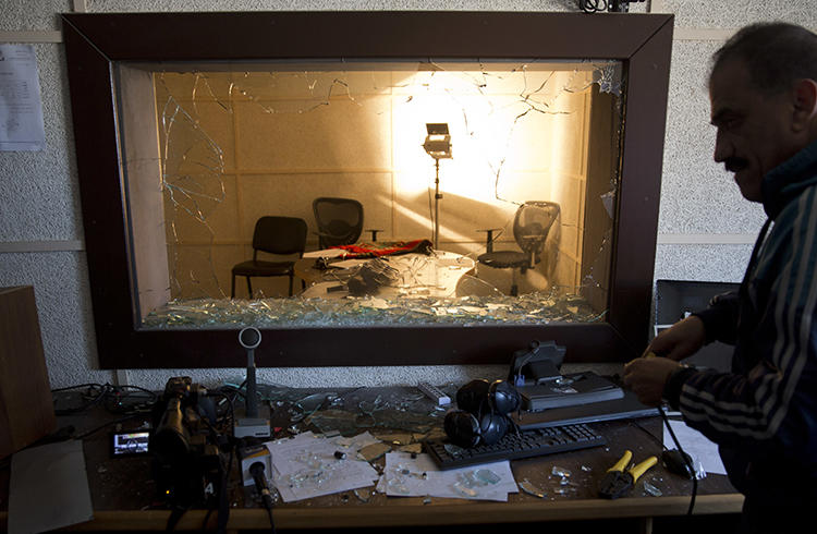 An employee checks the damage in a studio after a raid by assailants on the offices of the Palestinian Broadcasting Corporation in Gaza City on Friday, January 4, 2019. (AP Photo/Khalil Hamra)