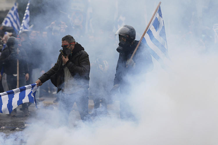 Demonstrators hold Greek flags in a cloud of tear gas during clashes at a rally in Athens on January 20, 2019. Several journalists were assaulted while covering the demonstration. (Thanassis Stavrakis/AP)