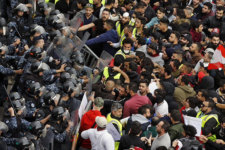 Anti-government protesters clash with riot police in central Beirut, Lebanon, on December 23, 2018. Multiple reporters were harassed and assaulted while covering the protests. (AP/Bilal Hussein)