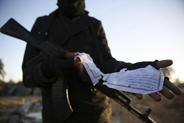 A February 2016 photo taken by Mohamed Ben Khalifa shows a member of the Libyan security forces with a document in Arabic describing weaponry found at the site of U.S. airstrikes on an Islamic State camp in Libya. Freelance photojournalist Ben Khalifa was killed during clashes on January 19. (AP/Mohamed Ben Khalifa/File)