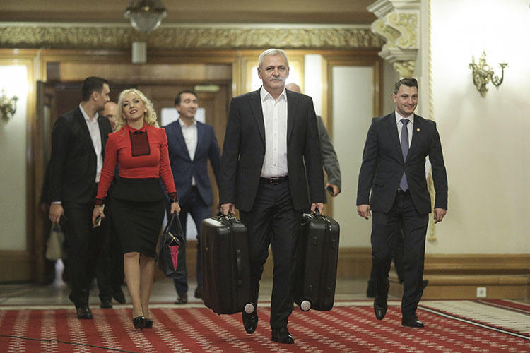 President of the ruling party Liviu Dragnea carries suitcases into parliament in November, as part of stunt mocking the Rise Project reporting. Romania's data protection authority has ordered the investigative outlet to reveal its sources. (Inquam Photos/Octav Ganea)