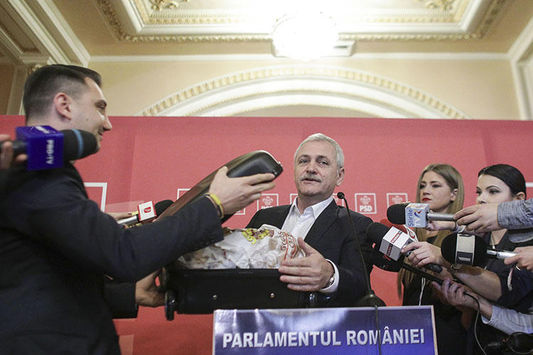 In response to a Rise Project report alleging corruption, based on documents provided in a suitcase, party leader Liviu Dragnea carried a case of donuts into parliament, which he said were from the investigative outlet. (Inquam Photos/Octav Ganea)