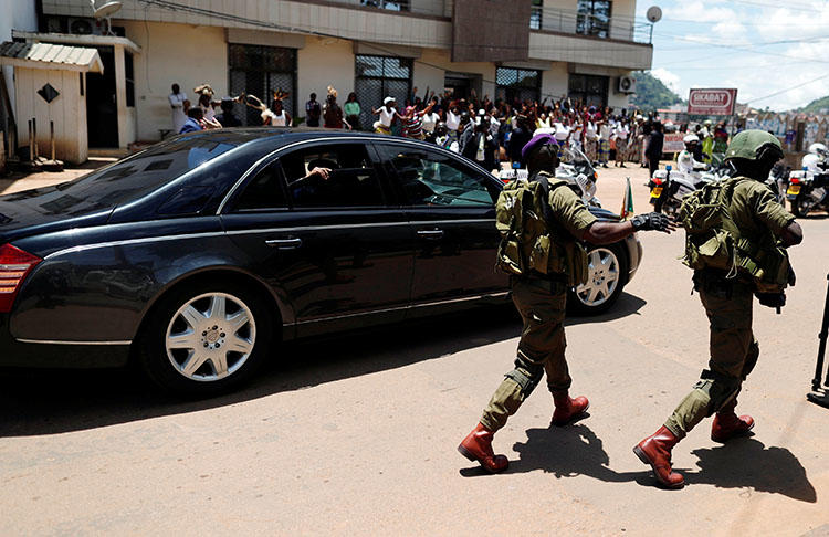 A security guard walks beside the car of Cameroonian President Paul Biya after casting his ballot in the presidential election in Yaounde, Cameroon, on October 7, 2018. Two Cameroonian journalists were detained while covering an opposition gathering in Douala on January 28, 2019. (Reuters/Zohra Bensemra)